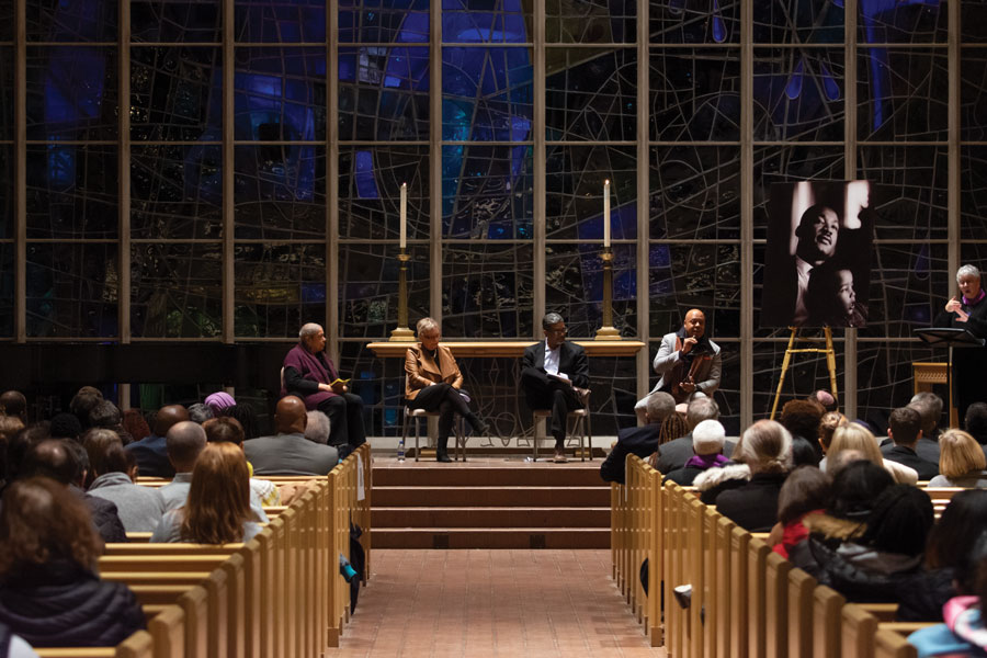 Panelists discuss black progress at the Martin Luther King Day candlelight vigil.