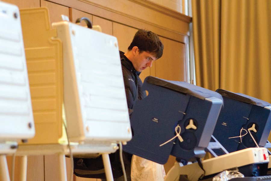 A+student+votes+at+a+voting+machine.+Voters+looking+to+register+in+Illinois+by+mail+or+online+must+do+so+by+Feb.+18+and+Feb.+29%2C+respectively.
