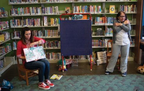 Evanston Public Library librarian Kerry Littel reads a story aloud as volunteer Evelyn Keolian shows a group of kids the sign for hug in American Sign Language. They work together to provide ASL storytime at the Chicago Avenue/Main Street Branch of EPL.