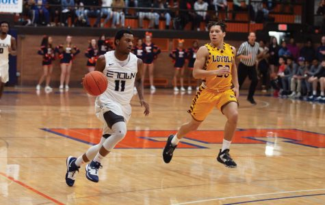 Junior Daeshawn Hemphill dribbles a basketball down the Beardsley Gym court as a Loyola Academy player runs beside him. Hemphill is part of the all-junior starting lineup on the Evanston Township High School boys varsity basketball team.