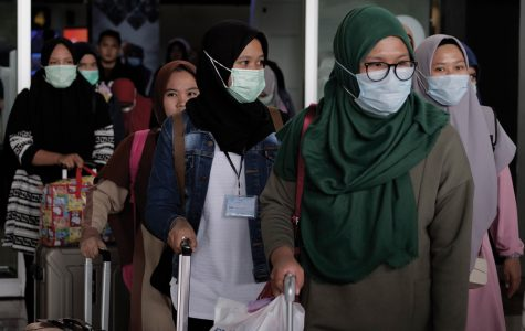 Airline passengers wearing face masks as a precaution to the outbreak of the coronavirus at the airport in Cengkareng, Indonesia, on Saturday, Feb. 1, 2020. Here in Chicago, though, experts generally agree that residents should be more concerned about catching the flu.