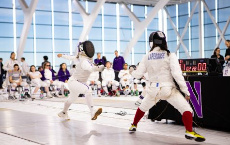 A Northwestern fencer strikes her opponent.