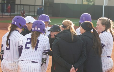 Northwestern holds a meeting near home plate. The Wildcats open their season this weekend.