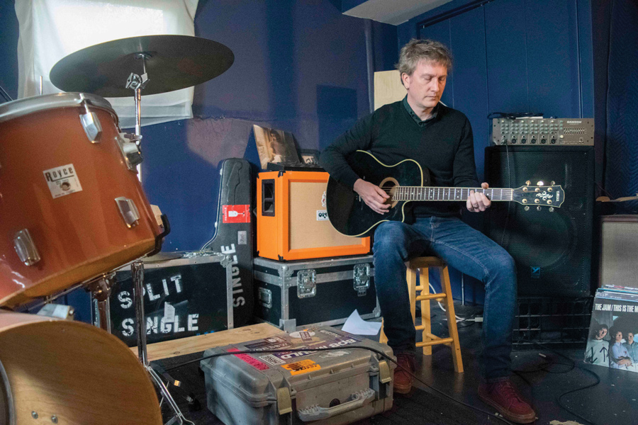 Jason Narducy plays guitar in his home practice space. Narducy wrote the score for the musical Verböten, which is based on his childhood band.