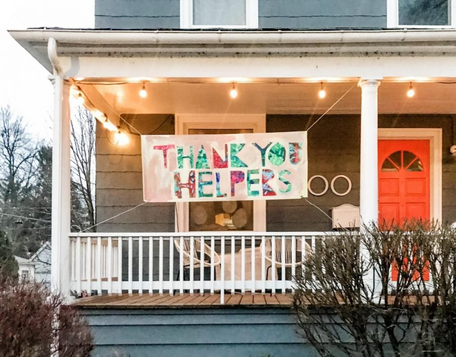 Amanda Freund hangs a banner outside her home. The banner was inspired by a Mister Rogers quote.