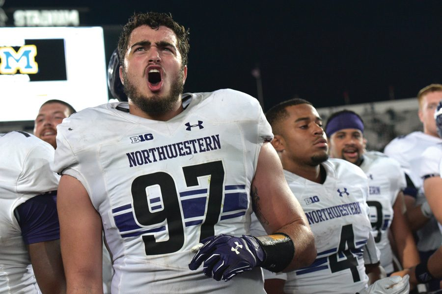 Joe Gaziano celebrates after a 2016 win. The former Northwestern defensive end was signed by the Los Angeles Chargers as an undrafted free agent on Saturday.