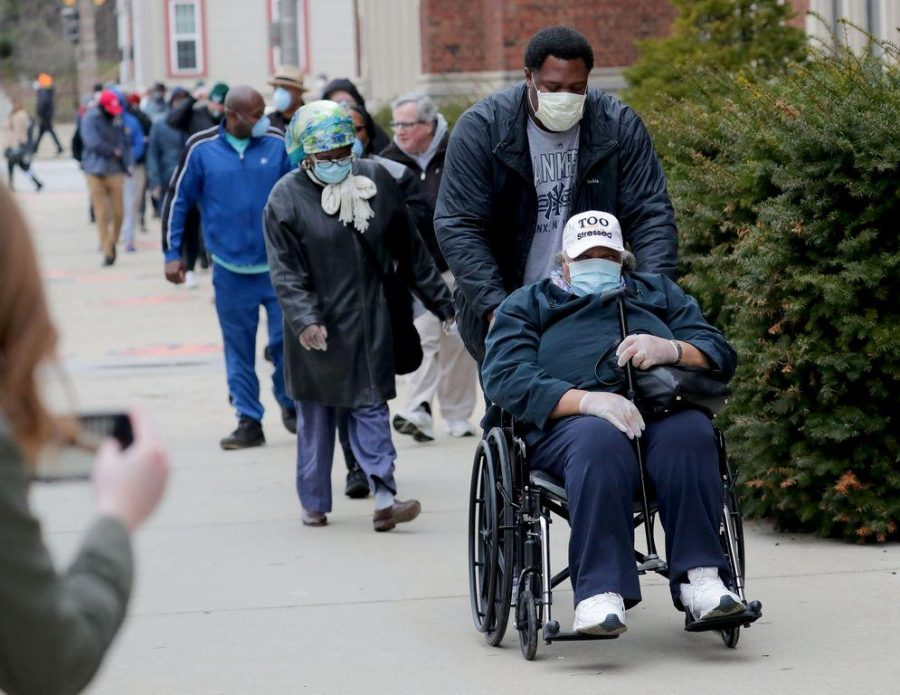 79 year old Rosie Redmon waits with her son, Deshawn Hudson to vote at Riverside High School, 1615 E. Locust St. in Milwaukee on Tuesday, April 7, 2020. The Wisconsin primary is moving forward in the wake of the coronavirus epidemic after Gov. Tony Evers sought to shut down Tuesday's election in a historic move Monday that was swiftly rejected by the conservative majority of the Wisconsin Supreme Court by the end of the day.