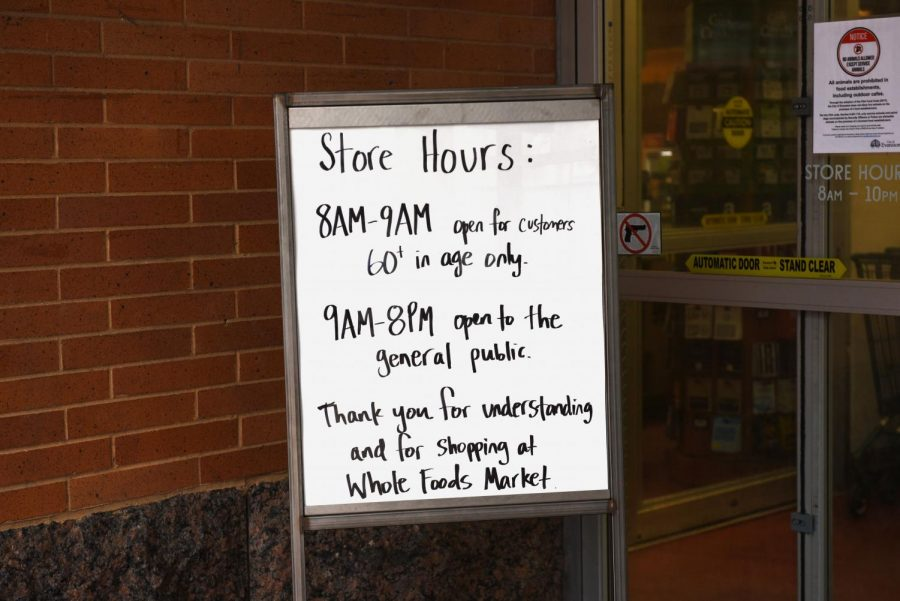 A sign outside Whole Foods Market. The grocery store opens an hour early for senior residents.
