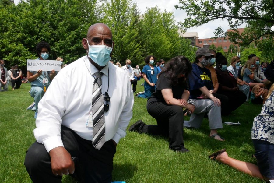 Evanston Hospital manager Bob Watkins kneels at Friday's vigil. Hundreds attended the event, part of a nationwide movement of medical professionals showing solidarity with the black community.