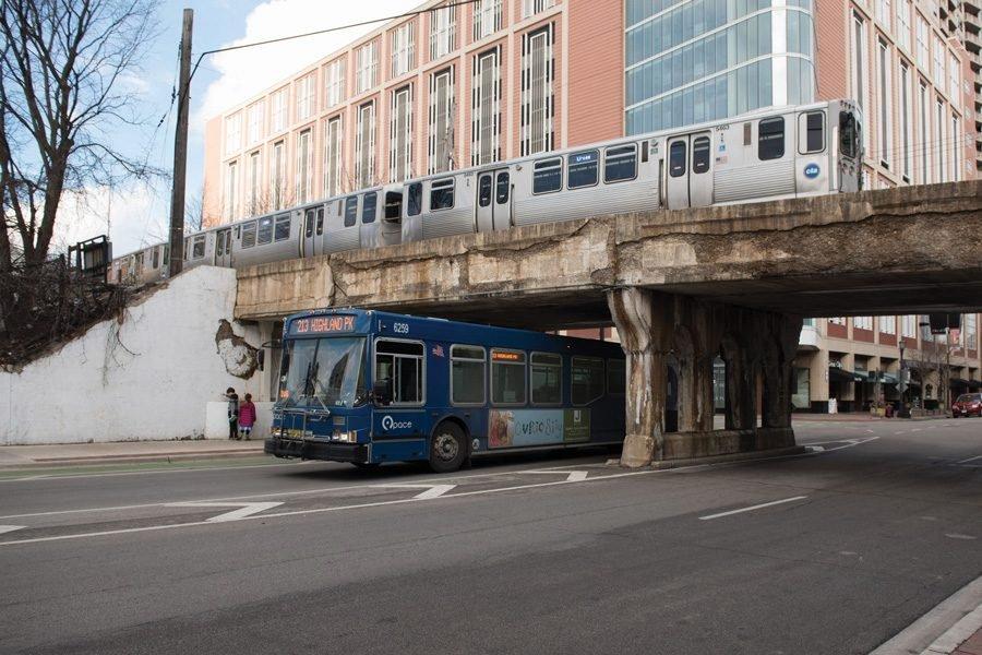 A Pace bus passes under the CTA Purple Line.