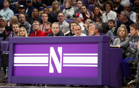 Chris Collins and Jim Phillips sit courtside at a game. The NCAA and its athletic programs face an uncertain future for collegiate sports.