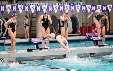A Northwestern swimmer leaps into the water.