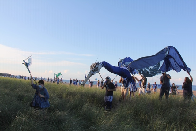 People work together to move a large blue heron. Members of Art of Spontaneous Spectacle and a public audience danced with bird masks during one performance.