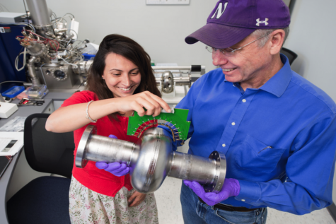 SQMS director Anna Grassellino and deputy director James Sauls hold a superconducting radio-frequency cavity at Fermilab. These cavities play a pivotal role in developing quantum technologies.