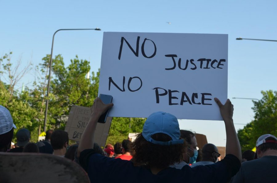 A protester holds up a sign on June 14, 2020 on S Martin Luther King Jr. Drive in Chicago. Protests calling for racial justice and an end to abusive policing have spread nationwide in response to the killings of George Floyd, Breonna Taylor and many others at the hands of the police.