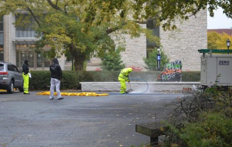 Members of the Facilities team pressure wash messages painted around The Rock.