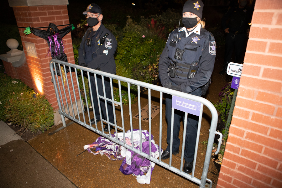 Northwestern police stand behind a University Facilities barricade outside President Schapiro's house. After removing the sign from the Arch and burning it, students left it at the feet of the officers.