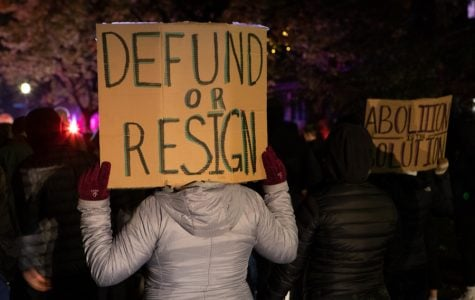 """One demonstrator holds up a sign reading """"Defund or Resign"""" at Monday night's march."""