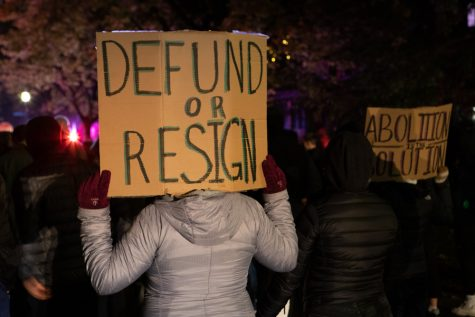"One demonstrator holds up a sign reading ""Defund or Resign"" at Monday night's march."