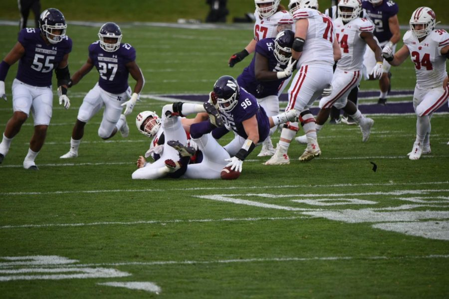 Junior defensive tackle Trevor Kent dives to recover a loose fumble. Northwestern forced five turnovers, including two fumble recoveries.