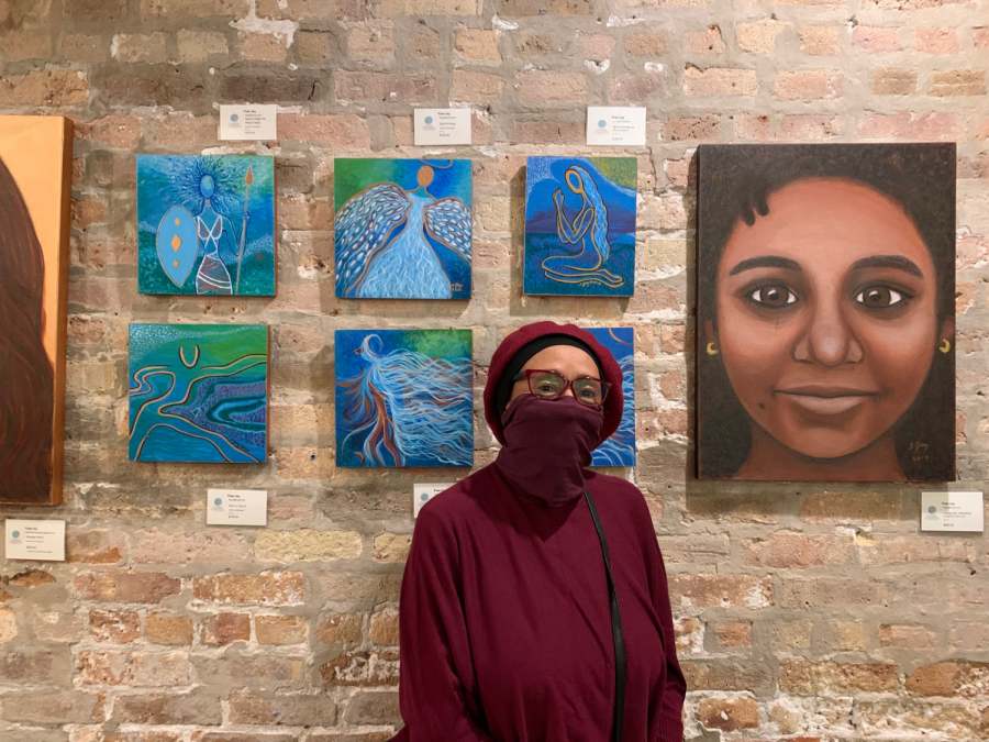 Fran Joy stands in front of her paintings at a show at Creative Coworking, 922 Davis St., on Saturday.