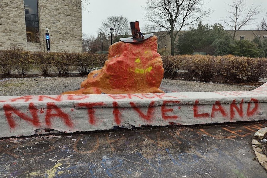 "The Rock. After it was given a Pilgrim hat in the days leading up to Thanksgiving, Indigenous graduate students responded by repainting it with phrases such as ""Native land"" and ""land back."""
