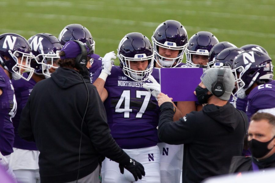 Northwestern players study a play on the field. The Cats had their first bye week of the season this week.