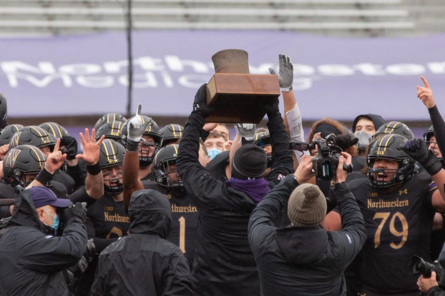 Pat Fitzgerald and his team celebrate the Land of Lincoln Trophy. The Cats are looking to win the Big Ten Championship this weekend against Ohio State.