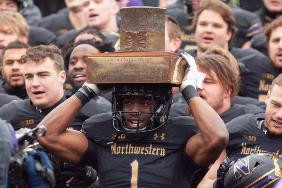 Northwestern running back Jesse Brown holds the Land of Lincoln Trophy on his helmet