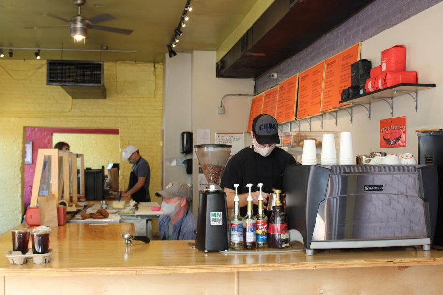 A+barista+prepares+a+patron%E2%80%99s+coffee+while+other+workers+prepare+bagels.+