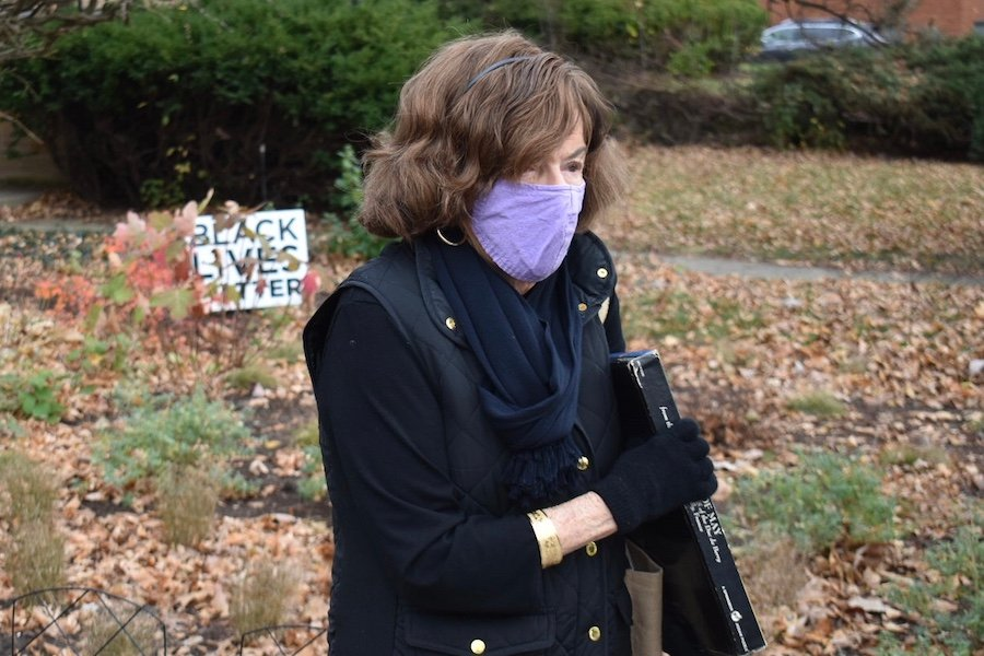 Eighth Ward Ald. Ann Rainey stands outside her home in a black jacket, wearing a purple mask, with a Black Lives Matter sign in the background.
