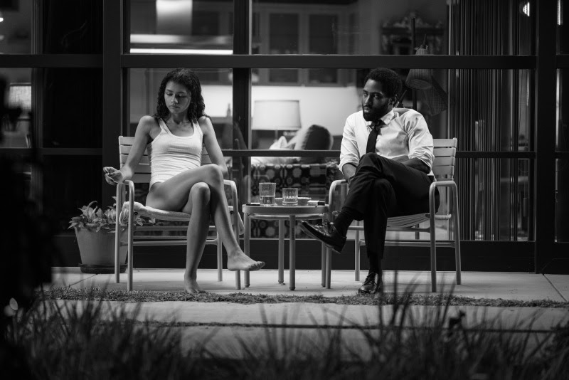 "Marie (Zendaya) and Malcolm (John David Washington) sit on their porch discussing their most recent argument in Netflix's ""Malcolm & Marie."""
