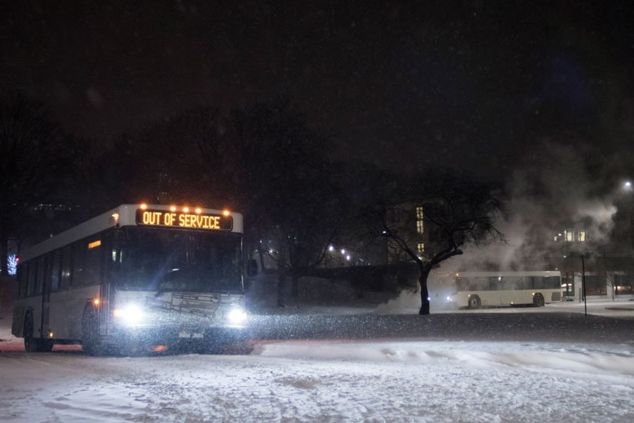 A bus traverses the snow. As temperatures plummet, the city announced a cold weather advisory.