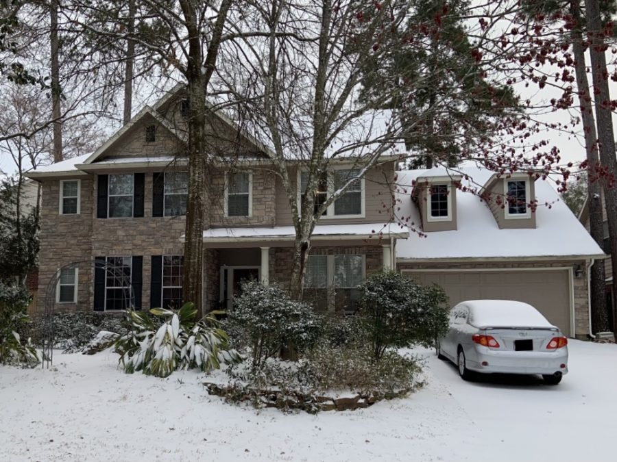 Front view of a two-story house covered in snow