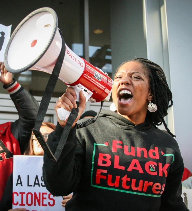 "A still from ""Unapologetic"" of Janae at a protest, speaking into a megaphone. She is wearing a t-shirt that reads"