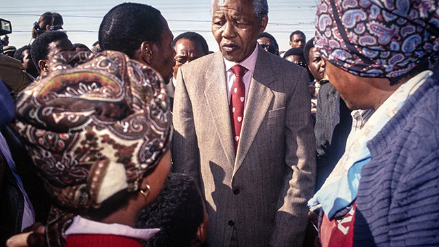 Nelson Mandela, centered, standing with a crowd.