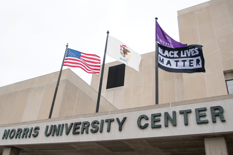 Awning of gray Norris University Center building, with the building name posted in dark gray lettering. Three flagpoles are nailed over the awning. From left to right they display the United States flag, the Illinois state flag, and the third one has a purple Northwestern University flag with a Black Lives Matter flag below that says the slogan in white lettering on a black background.