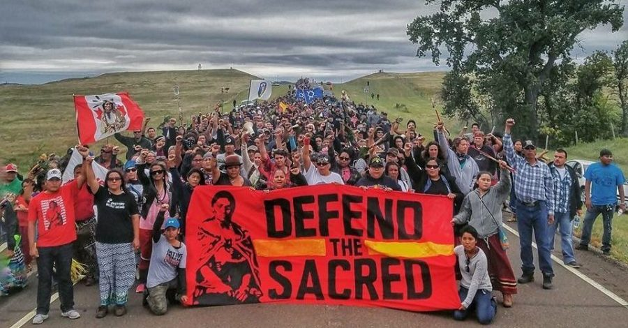 A large crowd of indigenous people, holding a red sign that reads Defend the Sacred.