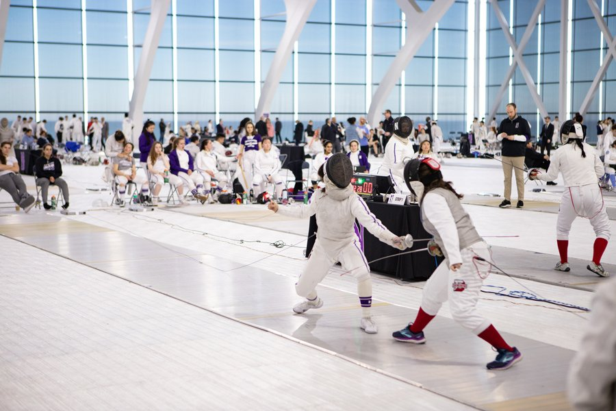 In foreground, two Northwestern fencers square off against opponents during a meet as both teams look on.