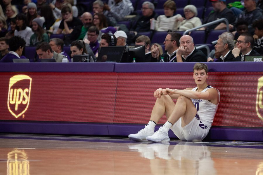 A Northwestern basketball player sits crouched in front of a red table