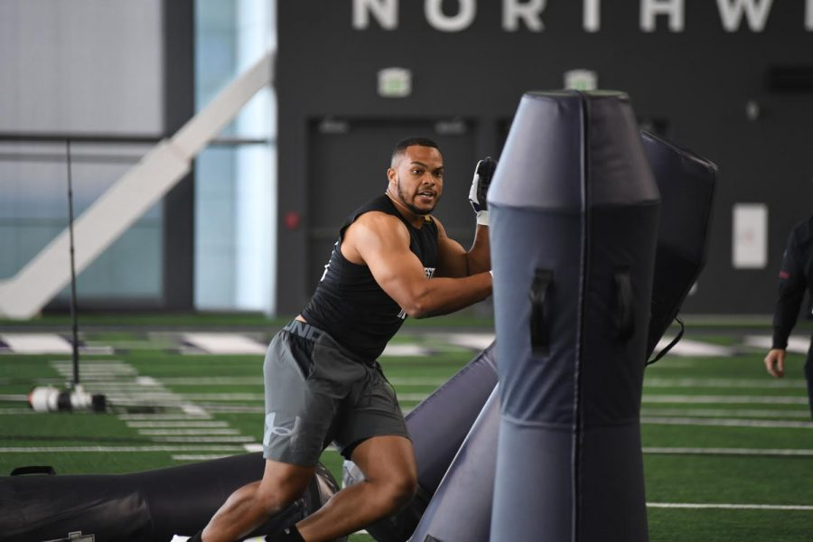 Northwestern football player hits beams as part of a football drill.