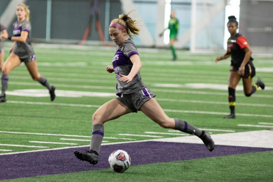 Freshman forward Ella Hase dribbles the ball up the field.
