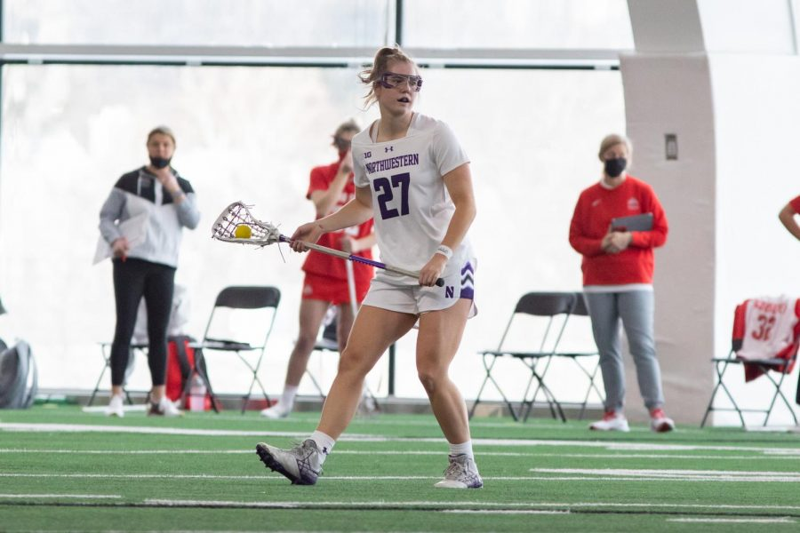 Northwestern lacrosse player holds a stick horizontally on the field.