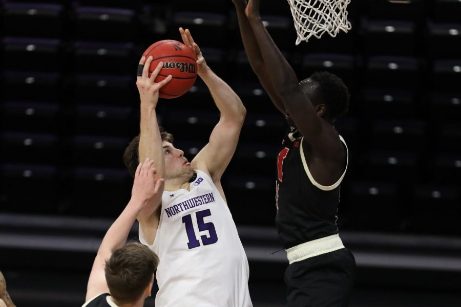 Male player from Northwestern prepares to attempt the game-winning layup over male player from Nebraska