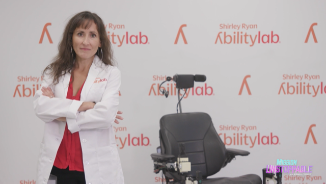 """Brenna Argall stands to the left of an autonomous wheelchair in front of a background that reads """"Shirley Ryan Ability Lab"""""""