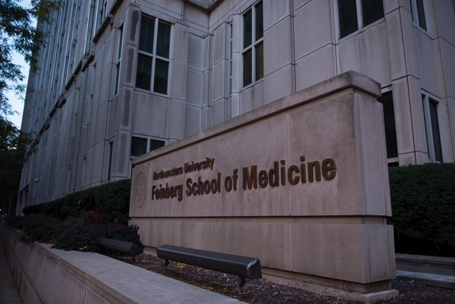 "A beige sign outside of a gray University building with the words ""Northwestern University Feinberg School of Medicine."" There are trees and shrubbery between the sign and the building."