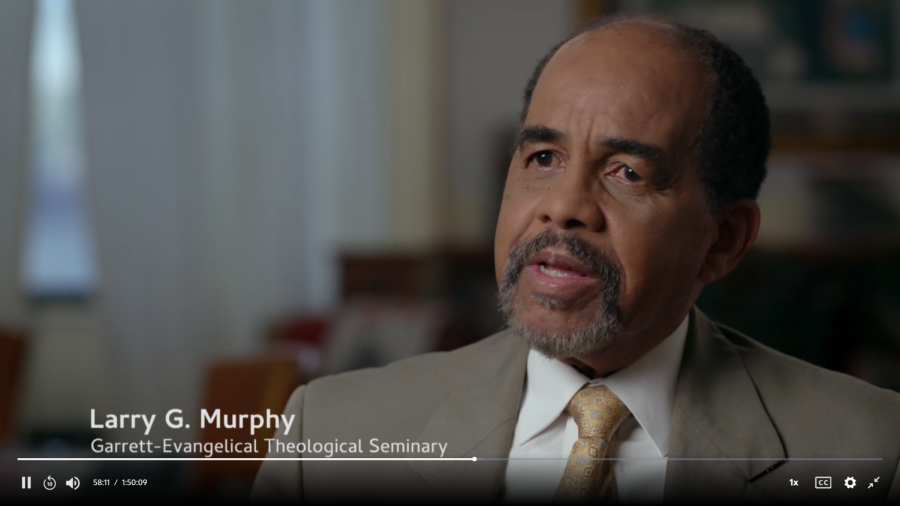 Dr. Murphy in a tan suit and tie mid-sentence. He is sitting in a church.
