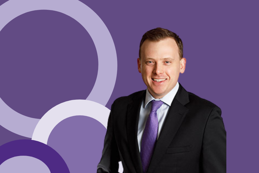 A photo of Luke Figora in a black suit with a purple tie against a purple background with varying circular shapes.