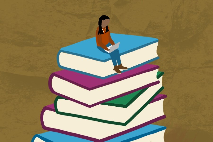A girl wearing an orange shirt sits reading a book on top of a stack of five blue, green and pink books.