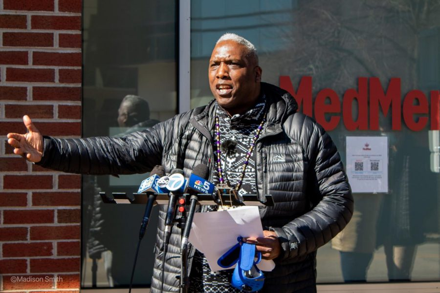 A man stands behind a press microphone stand in front of a MedMed glass storefront. He has sheets of papers in his hand and is gesturing towards a crowd of listeners.
